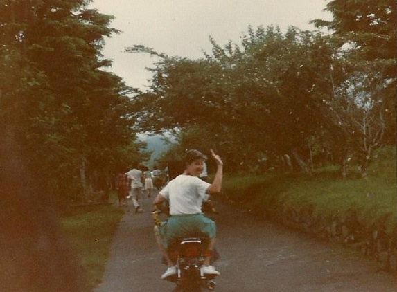 Mom wavin g'bye on a motor bike